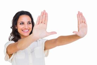 Pretty brunette holding up hands on white background.jpeg