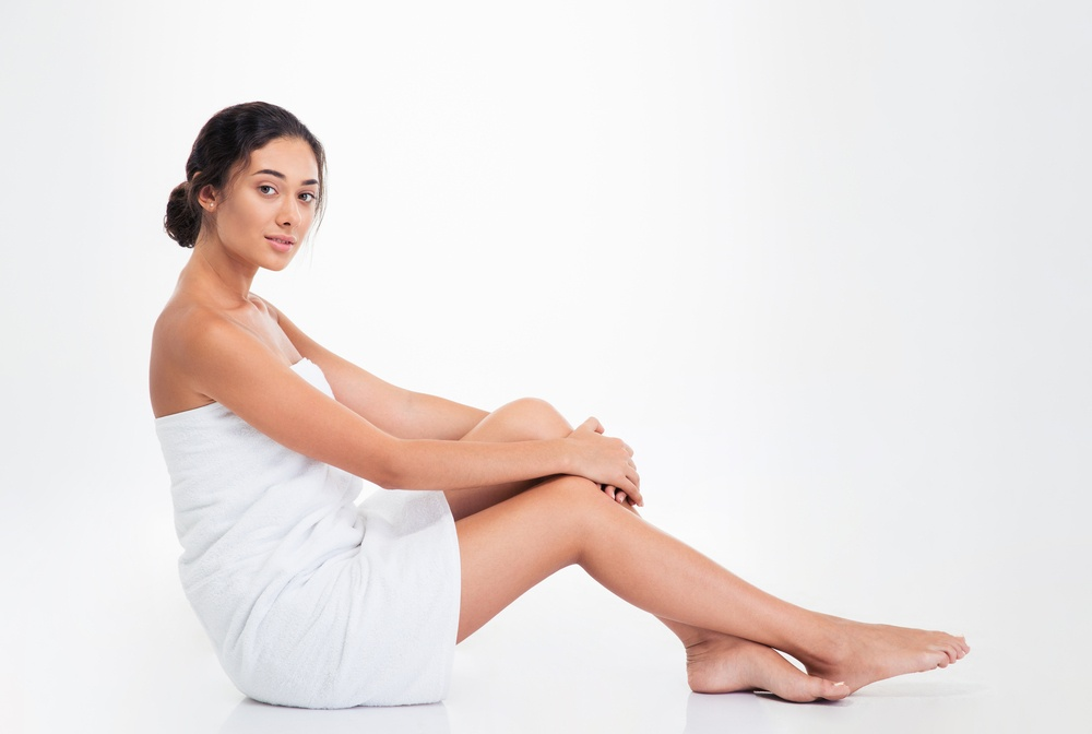 Beautiful young woman in towel sitting on the floor isolated on a white background