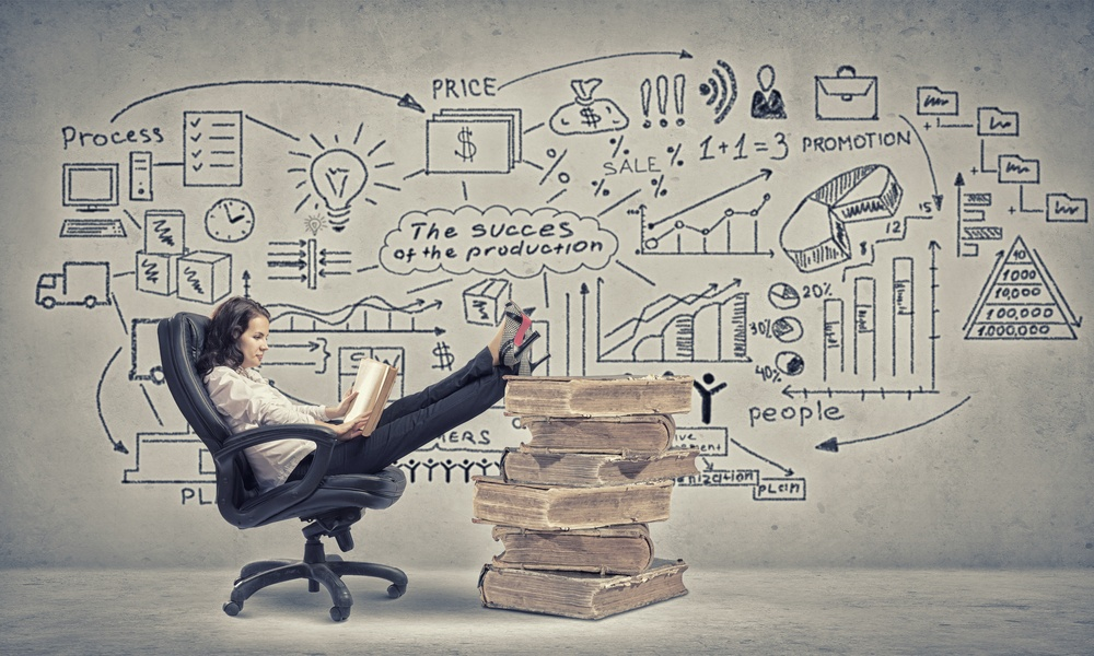 Young businesswoman sitting in chair with her legs on pile of books.jpeg